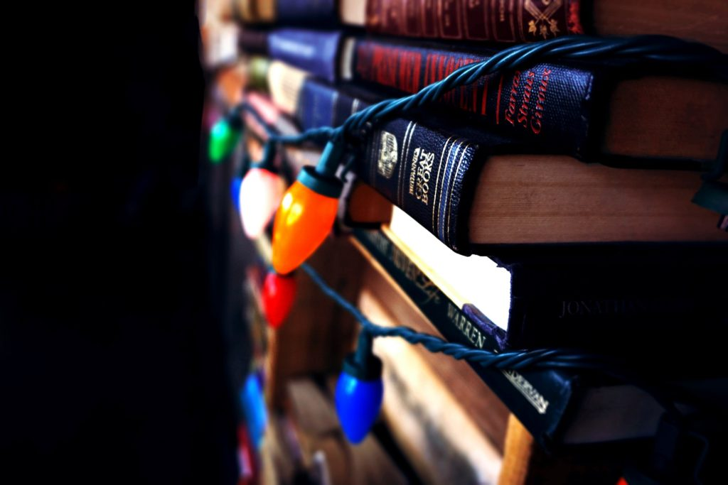 books stacked and draped in christmas lights