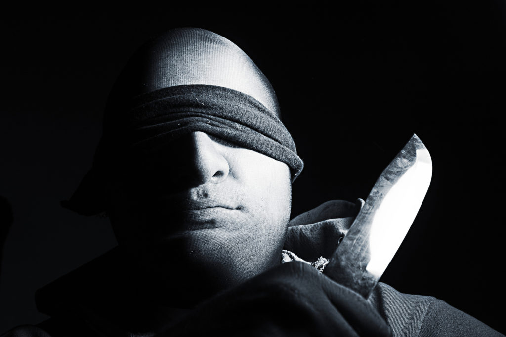 blind folded man with knife